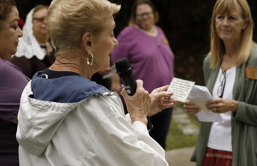 Volunteer Pat Goscienski reads the names of children