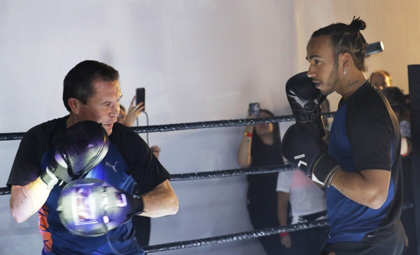 Mexican former boxing champion Julio Cesar Chavez, left, and British Mercedes driver Lewis Hamilton spar during a promotional event ahead of the Formula One race in Mexico City on Oct. 23.