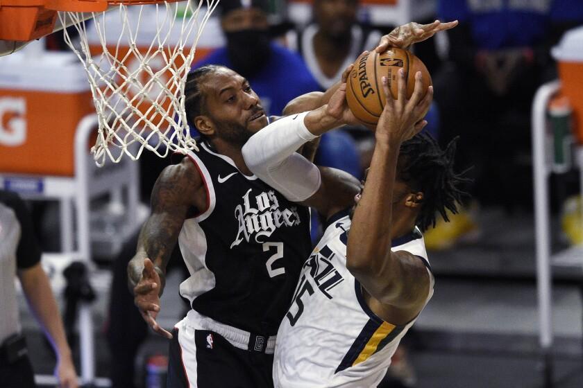 Clippers forward Kawhi Leonard, left, fouls Utah Jazz center Derrick Favors on a shot attempt Feb. 19, 2021.