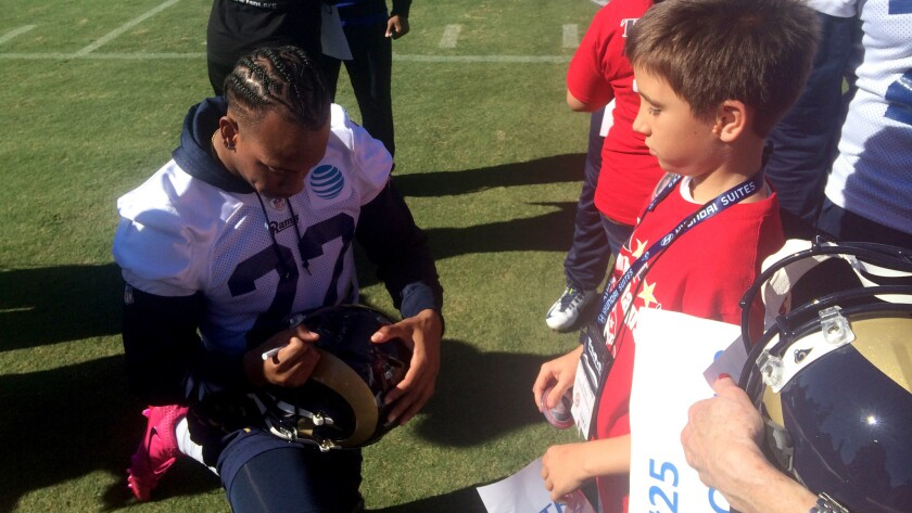 Cornerback Trumaine Johnson signs a helmet for Lucas McCaddon at Rams practice on Saturday.