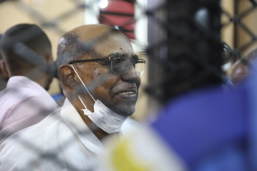 FILE - In this Sept. 15, 2020 file photo, Sudan's ousted president Omar al-Bashir sits at the defendant's cage during his trial a courthouse in Khartoum, Sudan, Tuesday, Sept. 15, 2020. The officer of Sudan's prime minister says International Criminal Court Prosecutor Fatou Bensouda is arriving in Khartoum Saturday, Oct. 17, to discuss cooperation with local authorities over the trial of those internationally wanted over war crimes and genocide in the Darfur conflict. Among those wanted by the court is former President Omar al-Bashir. (AP Photo/Marwan Ali)