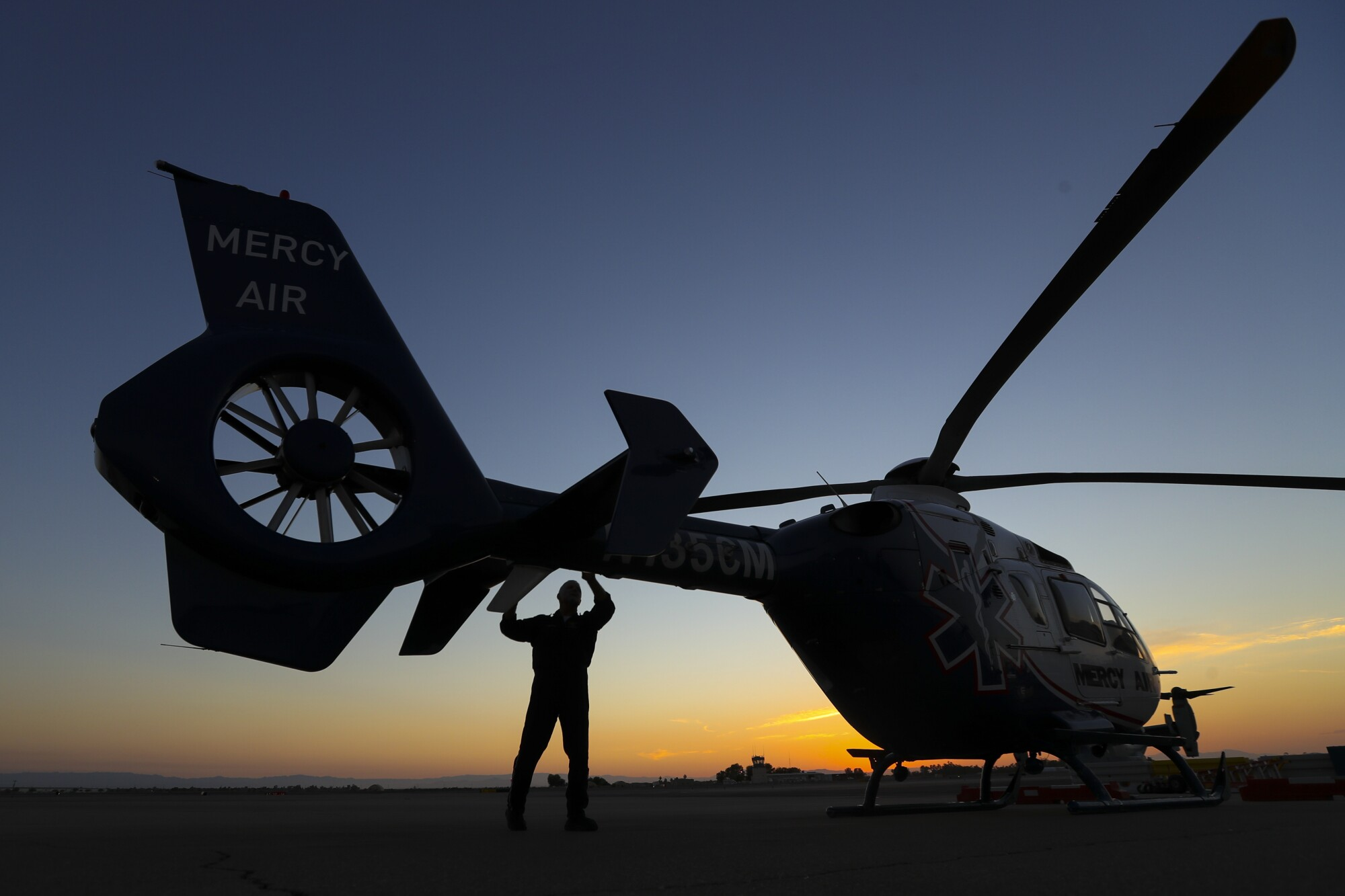Pilot Michael Bobeck at the start of his 12 hour night shift checks Mercy Air helicopter at Imperial County Airport.