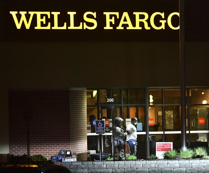 Police lead Ray Reco McNeary away from the Wells Fargo branch following a standoff of more than eight hours Thursday May 6, 2021, in St. Cloud, Minn. McNeary was disgruntled about a prior transaction, according to St. Cloud, police Chief Blair Anderson. (Dave Schwarz/St. Cloud Times via AP).