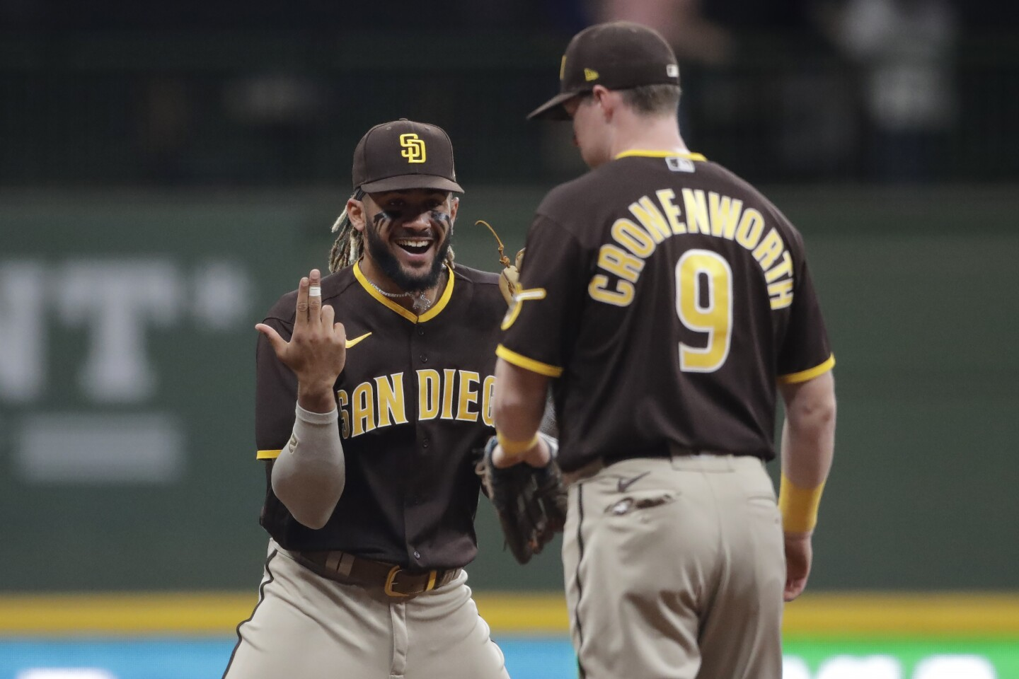 San Diego Padres' Fernando Tatis Jr. laughs with Jake Cronenworth (9) after a baseball game against the Milwaukee Brewers Wednesday, May 26, 2021, in Milwaukee. (AP Photo/Aaron Gash)