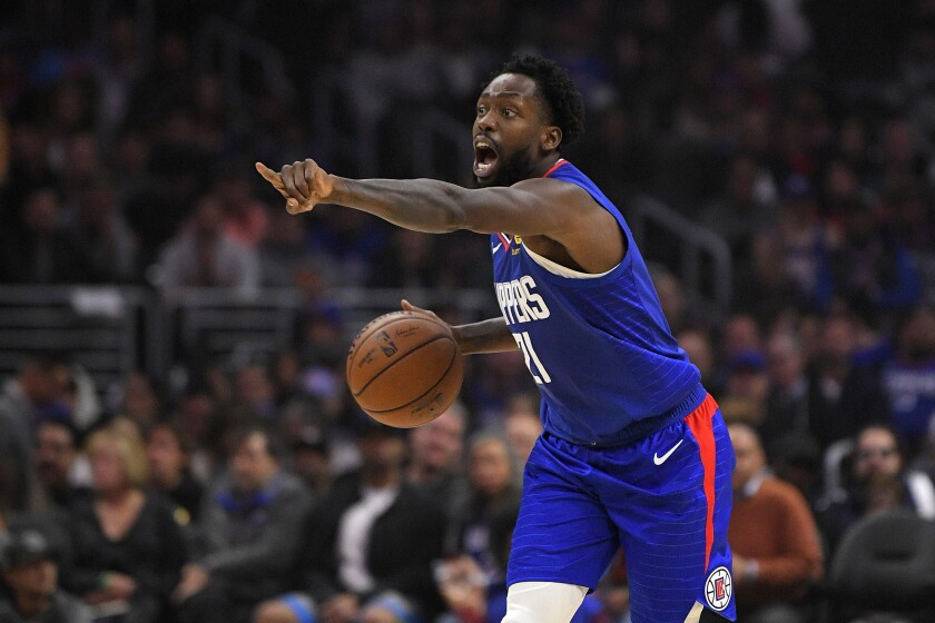 Clippers guard Patrick Beverley gestures while dribbling during a game.