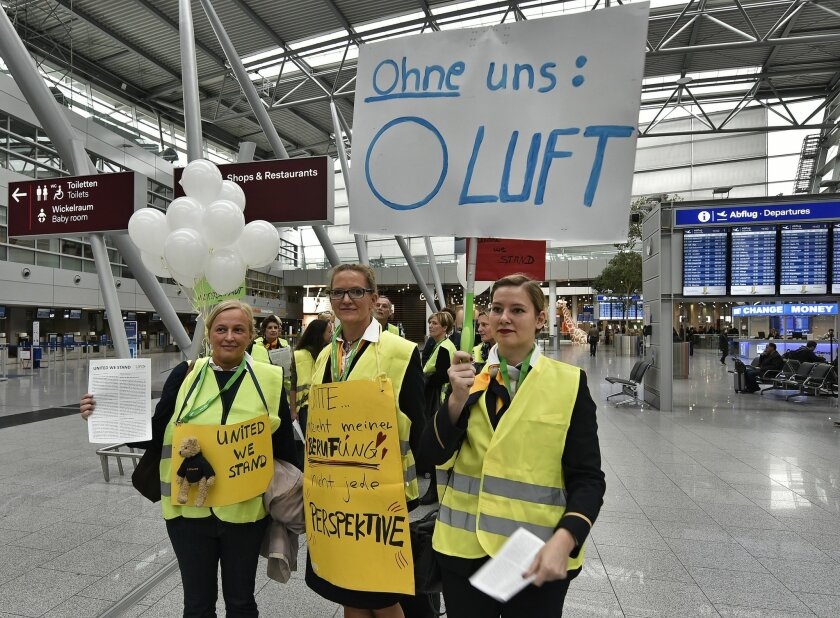 "Lufthansa flight attendants protest at the airport in Duesseldorf, Germany, Friday, Nov. 5, 2015. The poster reads ""without us - 0 air"". Germany's flagship airline, Lufthansa, canceled 290 flights on Friday as cabin crew workers went on strike at Frankfurt and Duesseldorf airports. The carrier said"