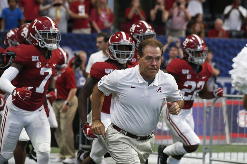 Alabama coach Nick Saban runs onto the field with his players before a game in August 2019.