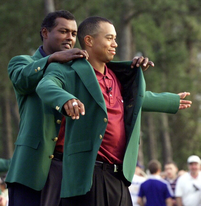 Tiger Woods, right, receives his Masters green jacket from 2000 champion Vijay Singh after winning the 2001 Masters at the Augusta National Golf Club in Augusta, Ga. on April 8, 2001.