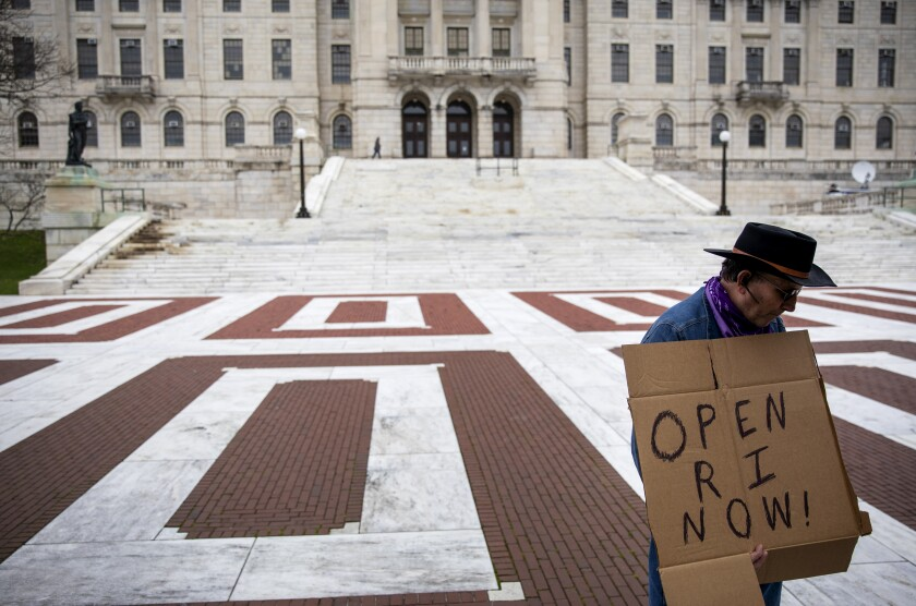 """FILE - in this May 1, 2020 file photo, James Dunn stands outside the statehouse in Providence, R.I. with a handmade sign. The smallest U.S. state has the longest name, and it's not sitting well for some in the George Floyd era. Officially, Rhode Island was incorporated as """"The State of Rhode Island and Providence Plantations"""" when it declared statehood in 1790. Now, opponents have revived an on-and-off effort to lop off the plantations reference, saying it evokes the dark legacy of slavery. (AP Photo/David Goldman, File)"""
