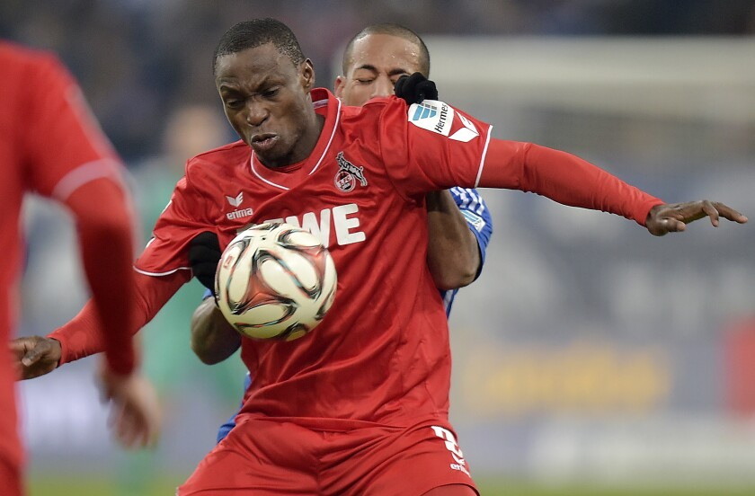 FILE - In this Saturday, Dec. 13, 2014 file photo, Cologne's Anthony Ujah from Nigeria, front, and Schalke's Dennis Aogo challenge for the ball during the German Bundesliga soccer match between FC Schalke 04 and 1. FC Cologne in Gelsenkirchen, Germany. Union Berlin striker Anthony Ujah has encouraged his fellow German soccer league players to be more proactive in the fight against racism. Ujah was the first Bundesliga player to react on social media to the killing of George Floyd, a handcuffed black man, who died on May 25 after a white Minneapolis police officer pressed his knee for several minutes on his neck. (AP Photo/Martin Meissner, File)