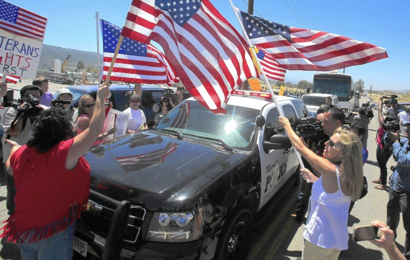 Protesters favoring stricter immigration enforcement turn away busloads of recently arrived women and children near a Border Patrol processing station in Murrieta last summer.