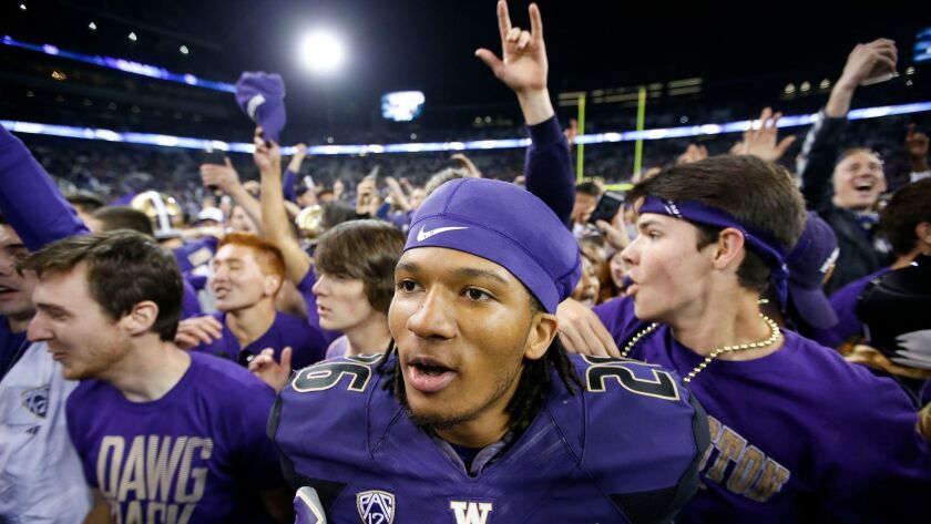 Washington cornerback Sidney Jones (26) celebrates as students rush the field after a game against Stanford.