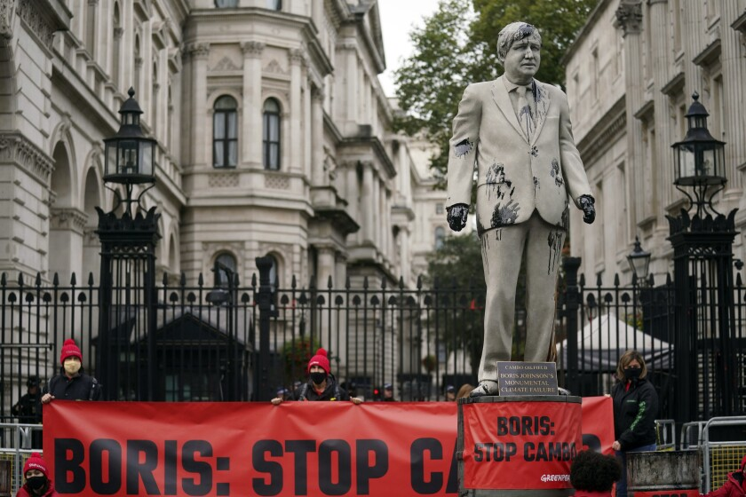 A statue of Prime Minister Boris Johnson is splattered with oil as campaigners from Greenpeace demonstrate against the Cambo oil field, outside Downing Street in London, Monday, Oct. 11, 2021. Activists in London chained themselves to an oil-spattered effigy of U.K. Prime Minister Boris Johnson Monday to urge him to reconsider his support for a permit to drill for oil west of the Shetland Islands. Some 40 protestors led by Greenpeace demonstrated near Johnson's Downing Street office to urge the government not to sign off a new drilling permit at the Cambo oil field. (Victoria Jones/PA via AP)