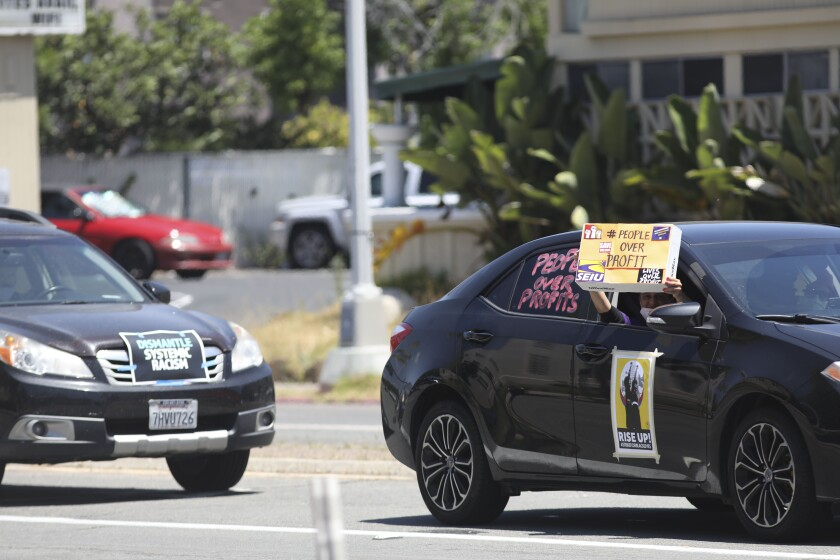 Motorists display signs supporting jail health workers in downtown San Diego Friday