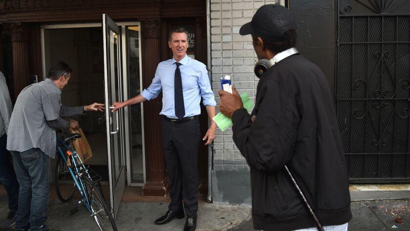 Gavin Newsom holds the door at a residence hotel in San Francisco on October 02, 2018.