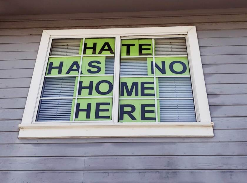 A window sign in Santee shows a response to a recent incident where a man wore a KKK hood inside a grocery store.