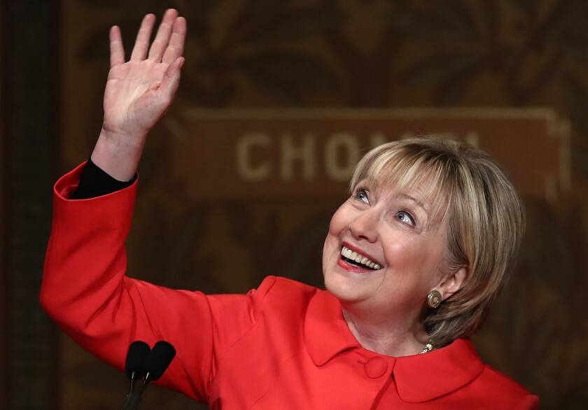 Former U.S. Secretary of State Hillary Clinton waves to students and guests while receiving a standing ovation before delivering remarks at Georgetown University.