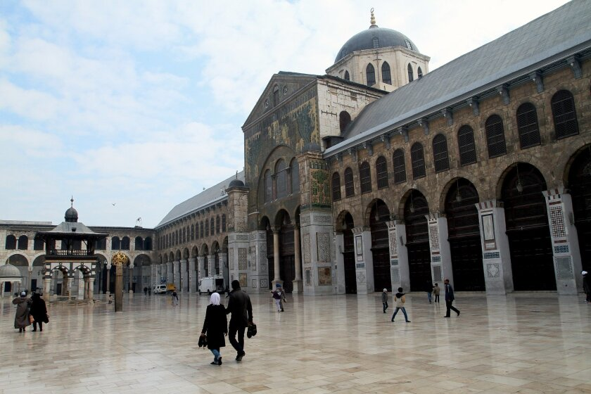 Syrian Muslims walk in the courtyard of the historic Umayyad Mosque before weekly prayers in Damascus, Syria, Friday, Dec. 6, 2013. One of the oldest mosques in the world, it was targeted by mortars a week earlier that killed four people in Syria's nearly 3-year old civil war. (AP Photo)