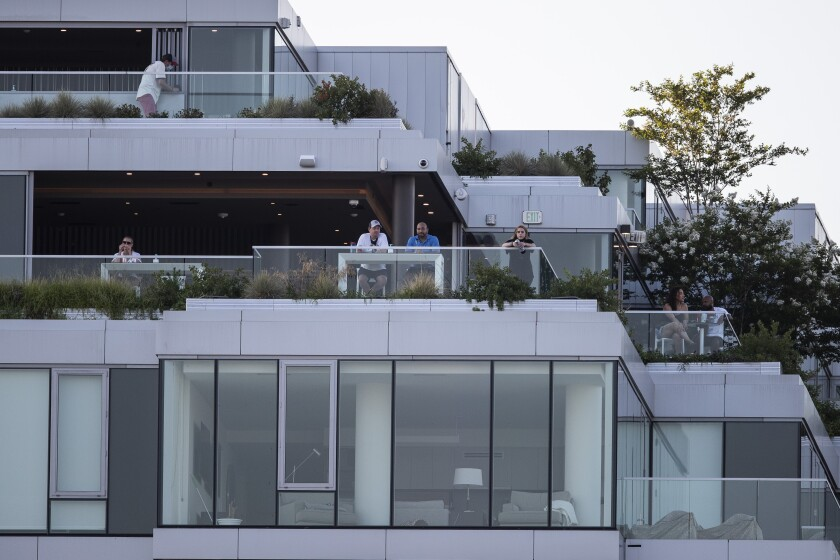 People watch from balconies of a building across the street during an exhibition baseball game between the Washington Nationals and the Philadelphia Phillies at Nationals Park, Saturday, July 18, 2020, in Washington. (AP Photo/Alex Brandon)