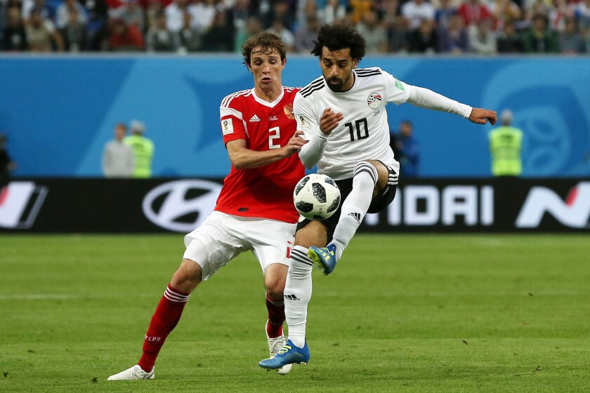Mohamed Salah of Egypt controls the ball unde rpressure of Mario Fernandes of Russia during the 2018 FIFA World Cup Russia group A match between Russia and Egypt at Saint Petersburg Stadium on June 19, 2018 in Saint Petersburg, Russia.