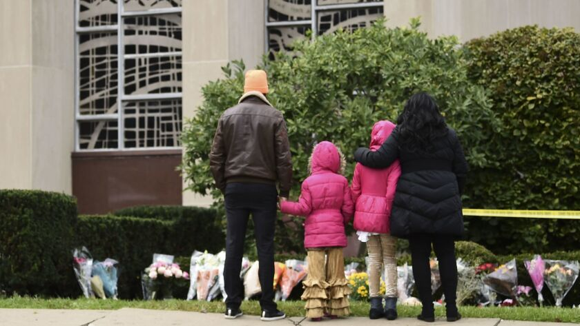 People stand in front of a memorial on Sunday outside of the Tree of Life Synagogue after a shooting there the day before left 11 people dead in the Squirrel Hill neighborhood of Pittsburgh.