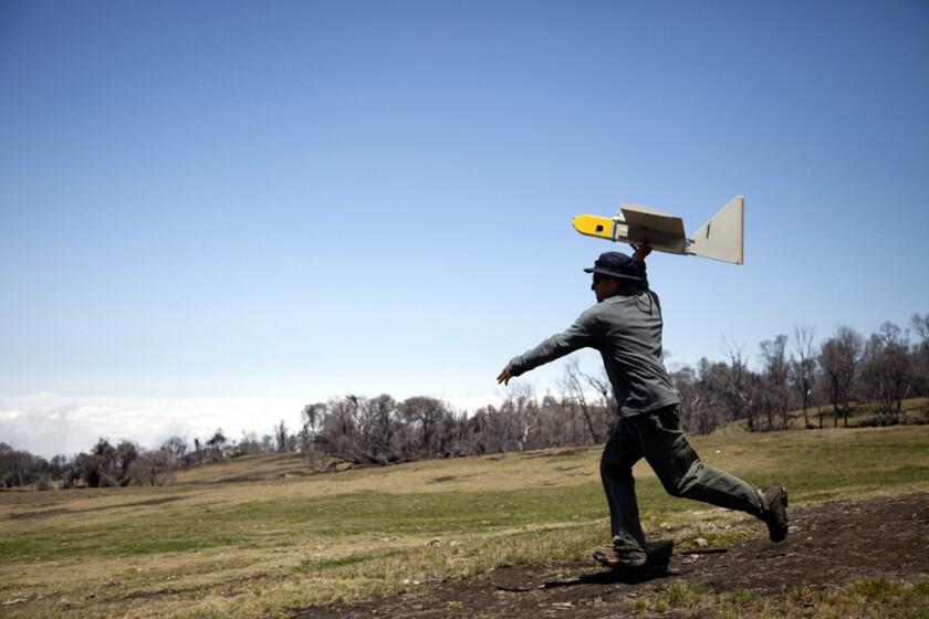 NASA research scientist Rick Kolyer launches a Dragon Eye drone.