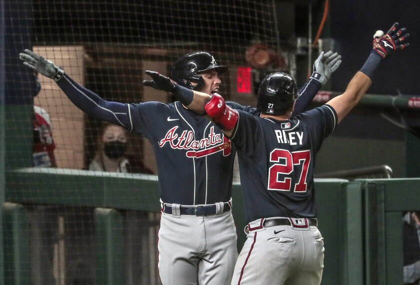 Freddie Freeman embraces Braves teammate Austin Riley who homered in the ninth inning in Game 1.