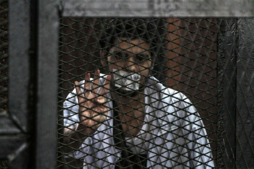 A defendent stands in the prisoners dock during the trial of 20 people on terror-related charges in Cairo.
