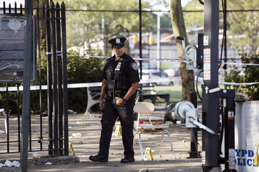 A police officer walks by yellow evidence markers at a playground in the Brownsville neighborhood in New York's Brooklyn borough on Sunday. Police said one man was killed and 11 others were injured in a shooting Saturday night.