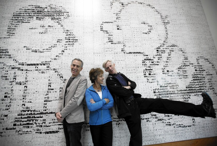 """Cartoonist Charles Schulz's son Craig, right, clowns around demonstrating his kicking prowess as Schulz's widow, Jeannie, and director Steve Martino look on at a mural depicting Charlie Brown about to be fooled by Lucy again, inside the Peanuts Museum in Santa Rosa, where they talked about """"The Peanuts Movie."""""""