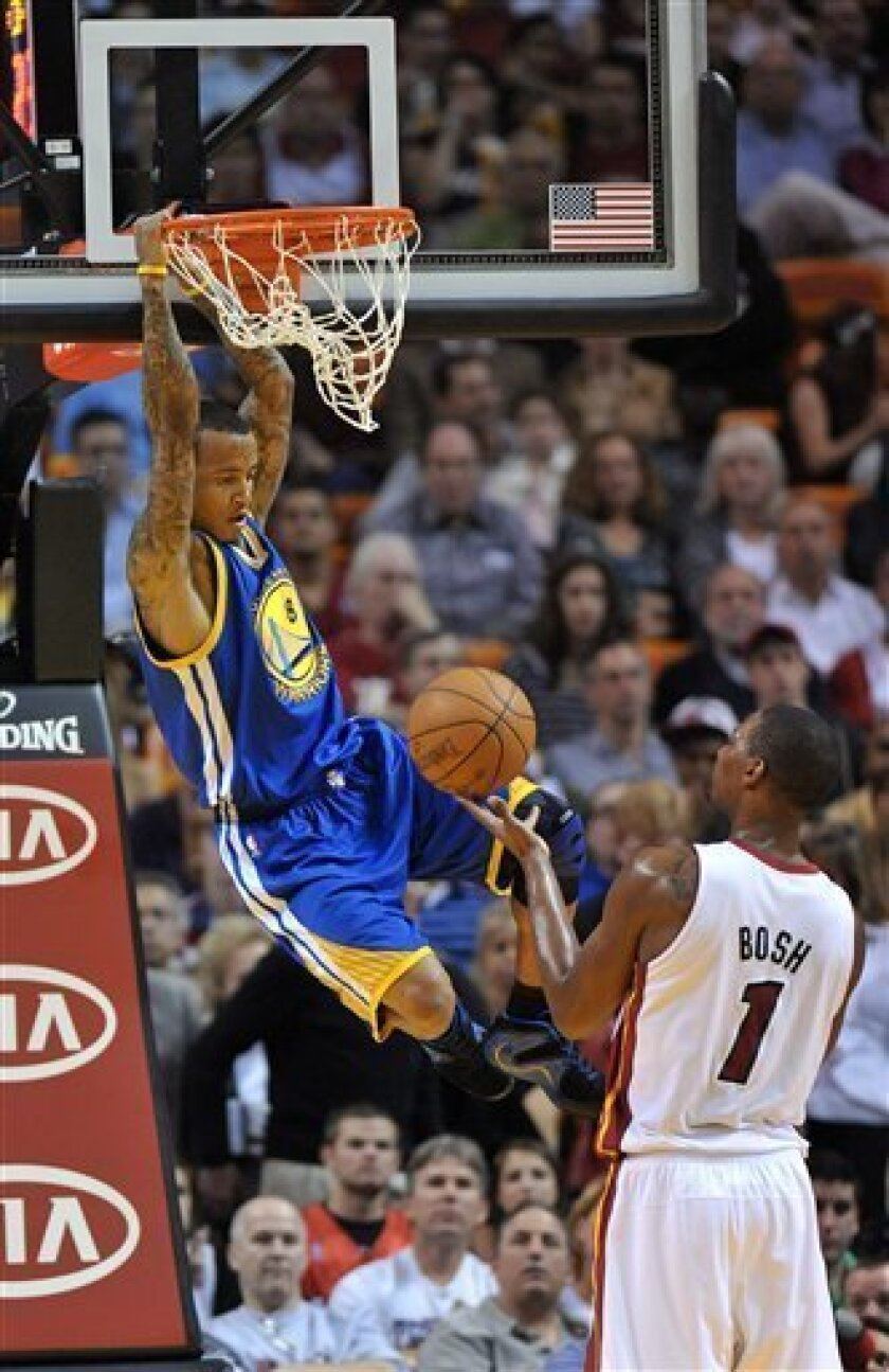 Golden State Warriors' Monta Ellis (8) dunks the ball in front of Miami Heat's Chris Bosh (1) during the first half of an NBA basketball game Saturday, Jan. 1, 2011, in Miami. (AP Photo/Steve Mitchell)
