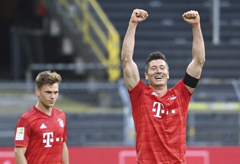 Munich's Joshua Kimmich, left, looks on as his teammate Robert Lewandowski, right, celebrates after the German Bundesliga soccer match between Borussia Dortmund and FC Bayern Munich in Dortmund, Germany, Tuesday, May 26, 2020. The German Bundesliga is the world's first major soccer league to resume after a two-month suspension because of the coronavirus pandemic. (Federico Gambarini/DPA via AP, Pool)