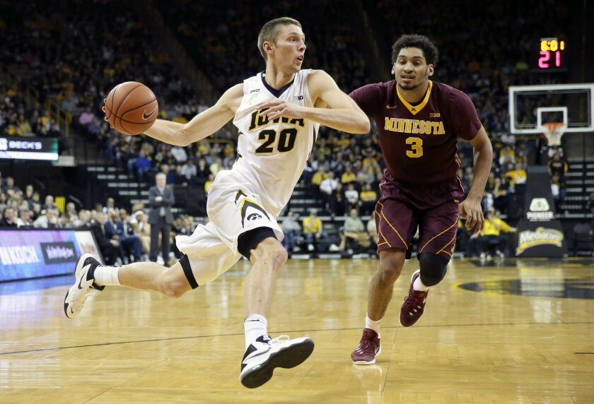Iowa forward Jarrod Uthoff drives to the basket past Minnesota forward Jordan Murphy, right, during the first half of an NCAA college basketball game, Sunday, Feb. 14, 2016, in Iowa City, Iowa. (AP Photo/Charlie Neibergall)