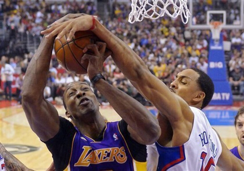 Los Angeles Clippers center Ryan Hollins, right, blocks the shot of Los Angeles Lakers center Dwight Howard during the first half of their NBA basketball game, Sunday, April 7, 2013, in Los Angeles. (AP Photo/Mark J. Terrill)
