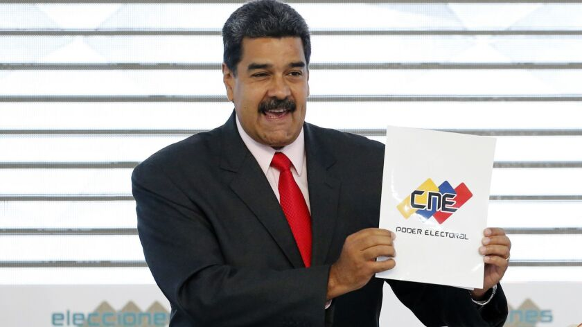 Venezuela's President Nicolas Maduro holds up the National Electoral Council certificate on May 22, 2018, declaring him the winner of the presidential election during a ceremony at CNE headquarters in Caracas, Venezuela.
