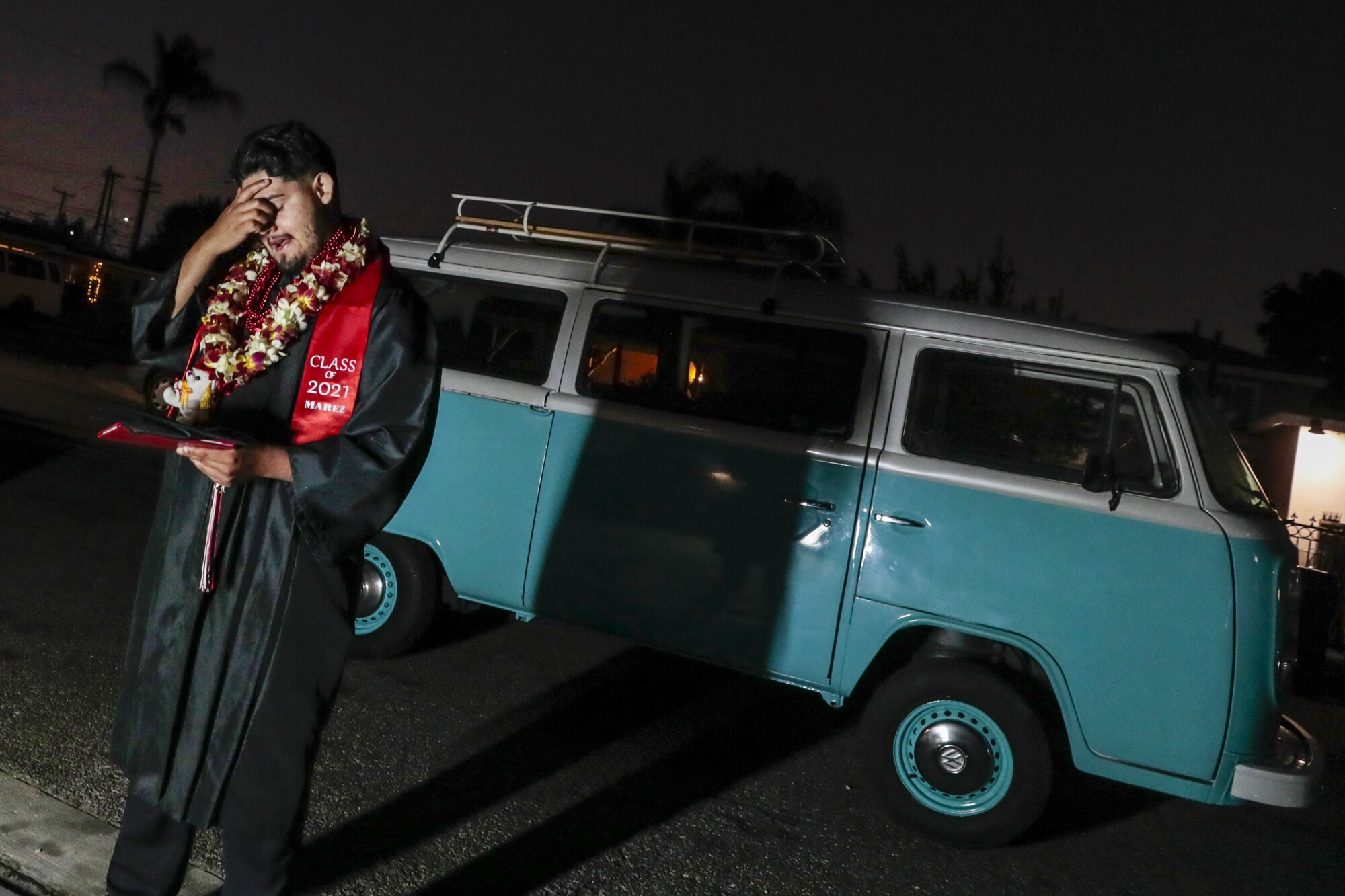 Cesar Martinez composes himself while having photos taken in front of a vintage VW van he helped his brother restore.