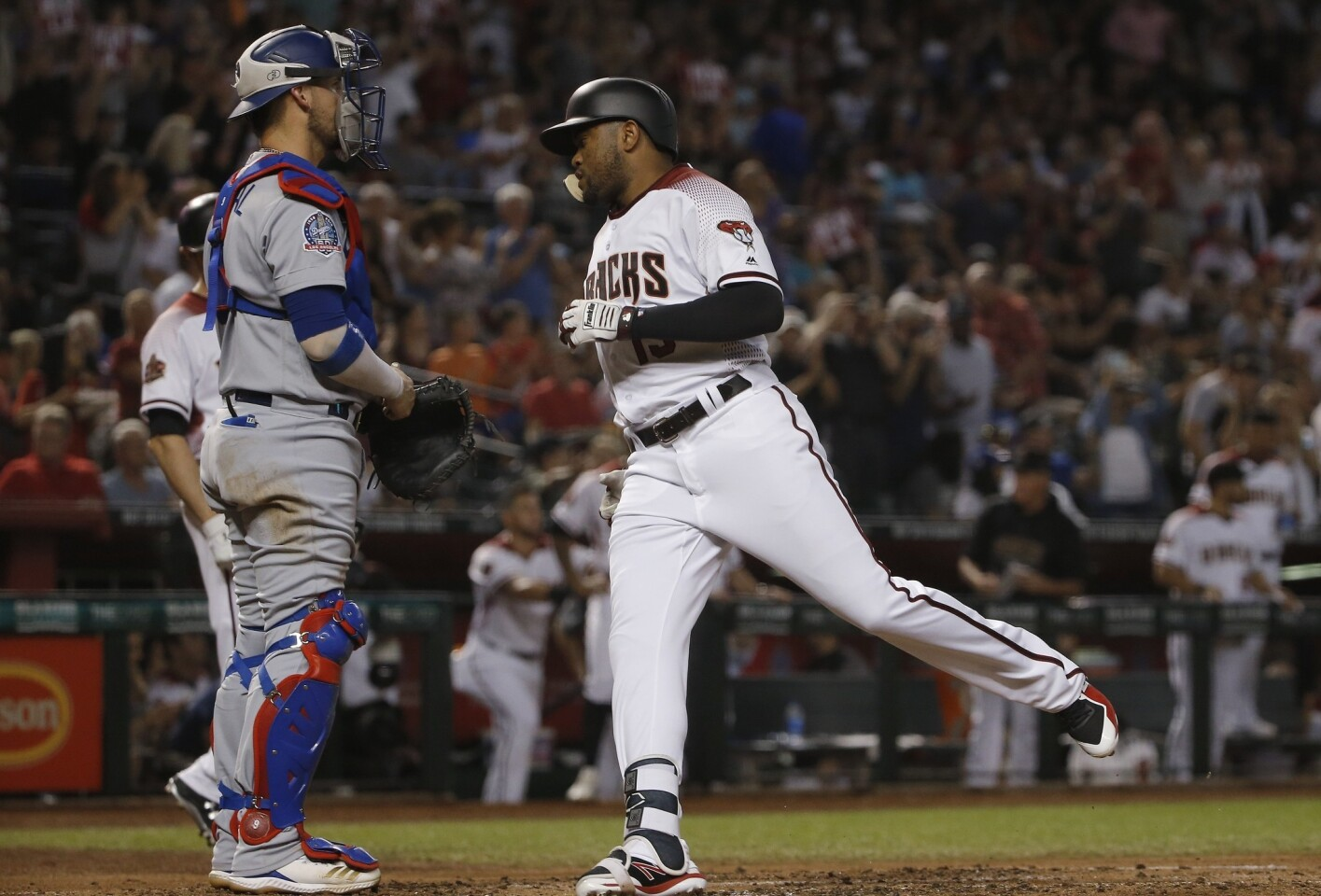 Arizona Diamondbacks' Socrates Brito, right, crosses home plate after hitting a home run as Los Angeles Dodgers catcher Yasmani Grandal, left, stands by during the second inning of a baseball game Wednesday, Sept. 26, 2018, in Phoenix. (AP Photo/Ross D. Franklin)