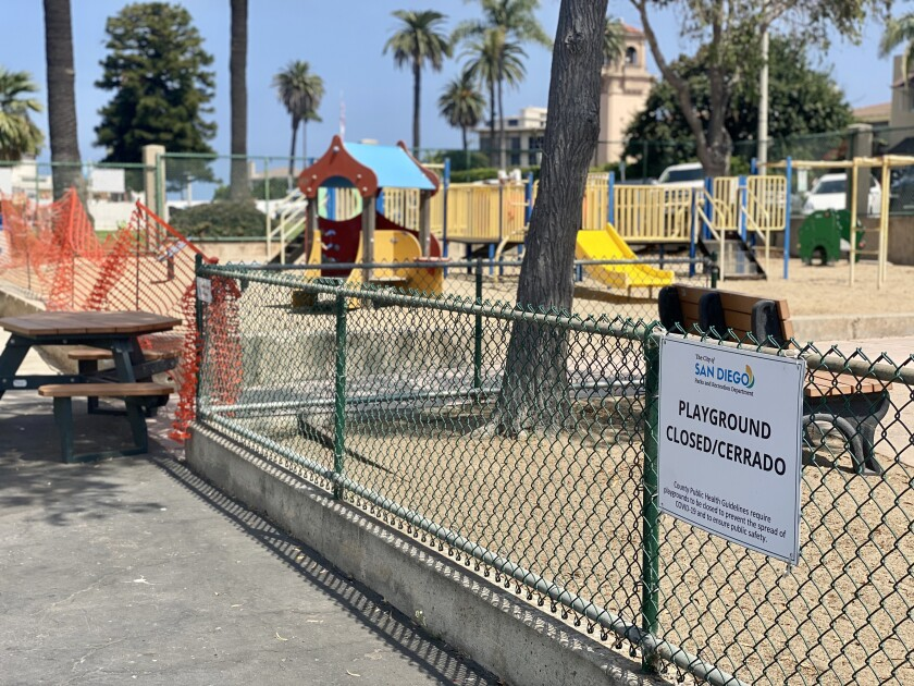 The La Jolla Recreation Center playgrounds are closed off by plastic orange fencing, with signs prohibiting their use.