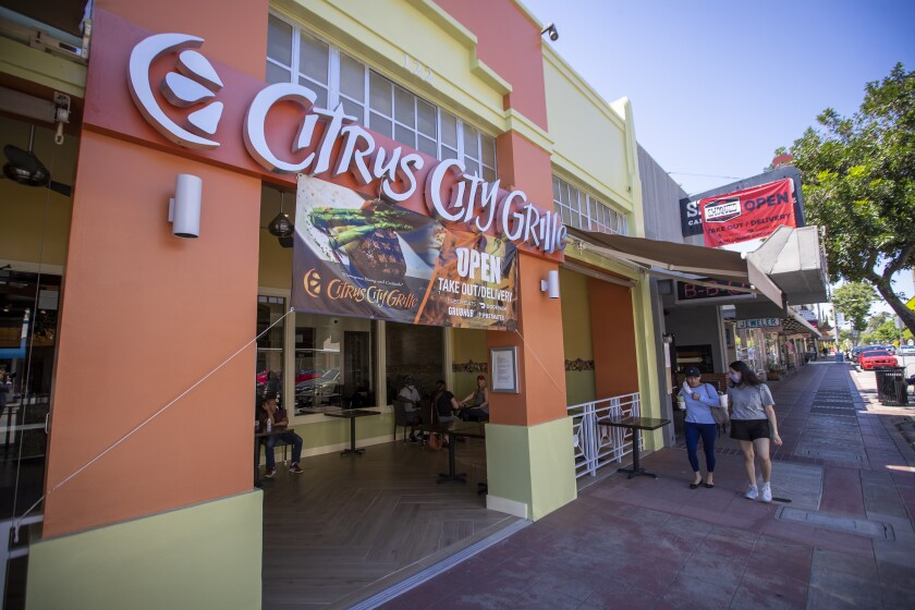Signs hang at Citrus City Grille and Smoqued California BBQ in Orange as pedestrians walk by Thursday.