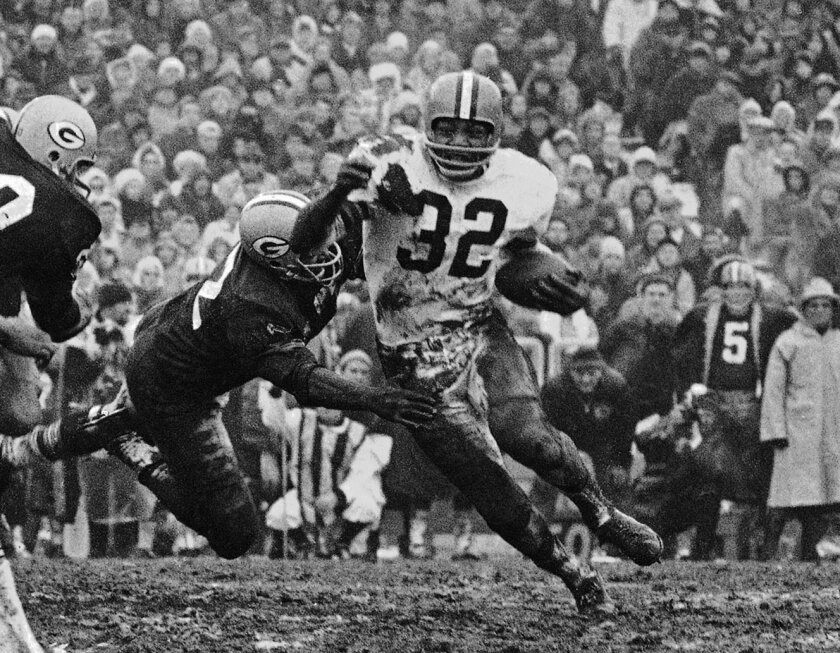 FILE - In this Jan. 2, 1966,  file photo, Cleveland Browns' Jim Brown (32) turns the corner as a Green Bay Packer defender swings with him during a football game in Green Bay, Wisc. The greatest Cleveland Brown of them all is being immortalized.  Hall of Fame running back Jim Brown, one of the most