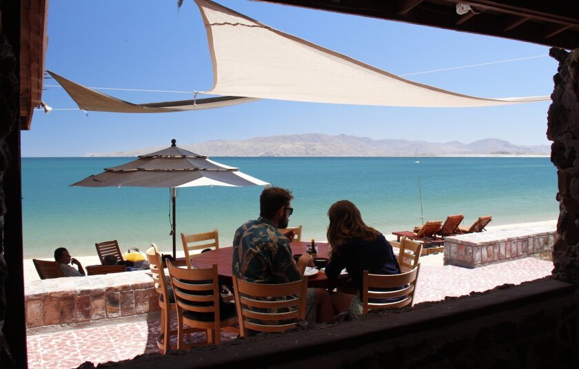 A young couple, biking down the length of Baja, stop for lunch at the picturesque Alfonsina's Restaurant on Gonzaga Bay.