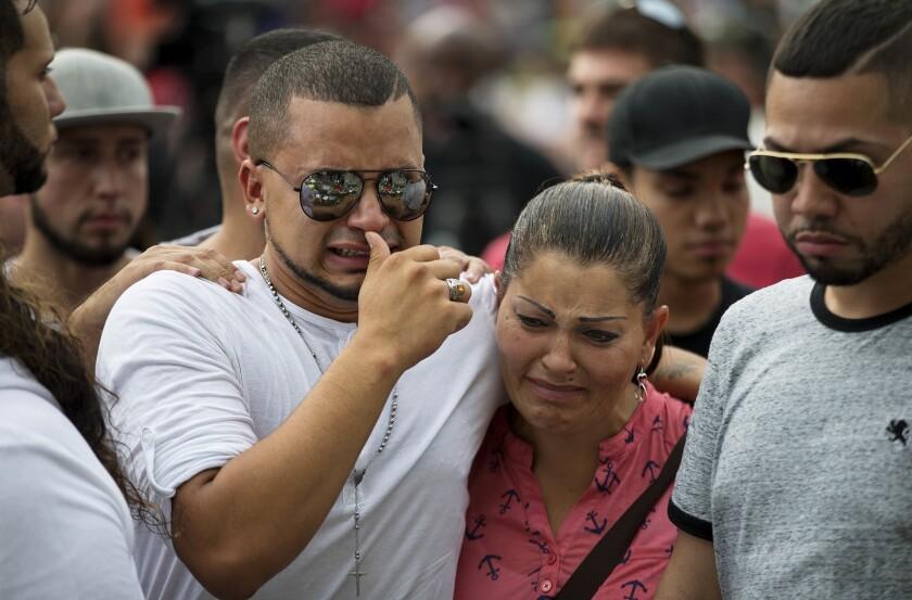 Victor Baez (izquierda) llora con Iris Febo mientras recuerdan a sus amigas Amanda Alvear y Mercedez Flores, fallecidas en una balacera en el club nocturno gay Pulse, durante una visita a un monumento de recuerdo improvisado, el 13 de junio de 2016, en Orlando, Florida. (AP Foto/David Goldman)