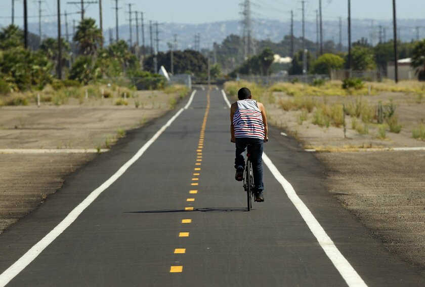Construction was completed on a 1.8-mile segment of the Bayshore Bikeway along Bay Boulevard between H and Palomar streets in Chula Vista in March. Here, a bicyclist rides on the paved path. The entire bikeway should be finished in five years.