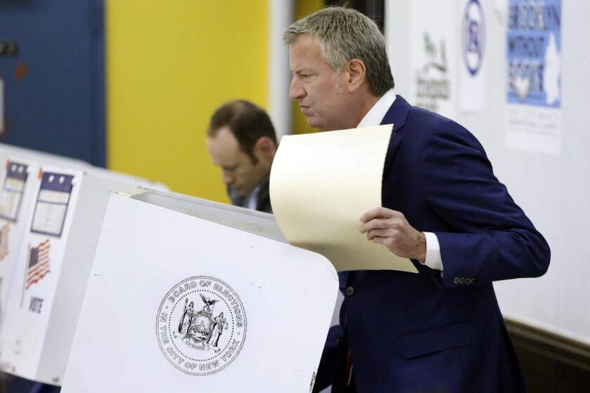 New York Mayor Bill de Blasio holds his ballot after voting at the Park Slope Library, in the Brooklyn borough of New York, Tuesday, Nov. 7, 2017.