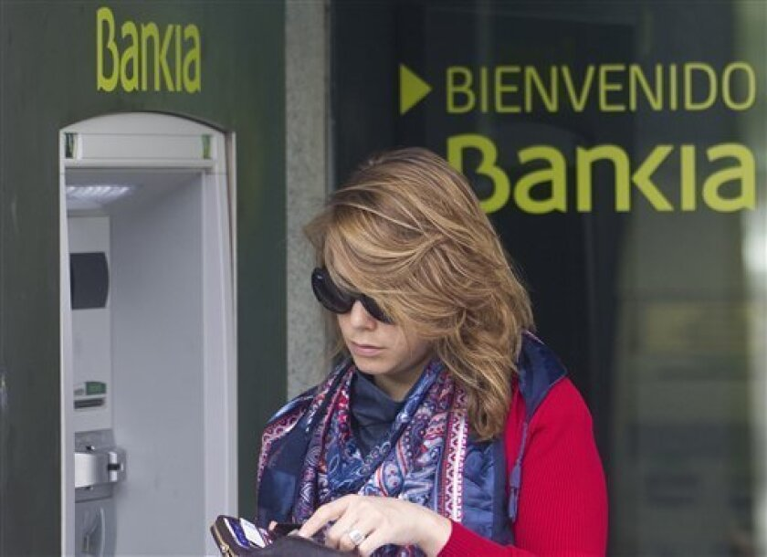 A woman uses an ATM cash point machine at a branch of the Bankia bank in Madrid Thursday May 17, 2012. A recently nationalized Spanish bank's shares plummeted Thursday after a newspaper said depositors were rushing to withdraw money, while the country paid sharply higher interest rates in a debt au