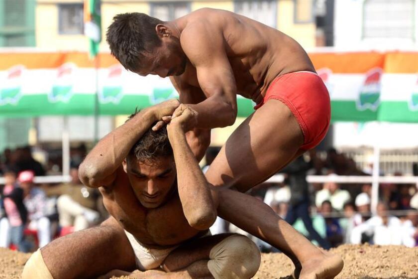 Luchadores indios en acción durante una competencia de lucha tradicional india, también conocida como Kushti, en Bhopal, India. EFE