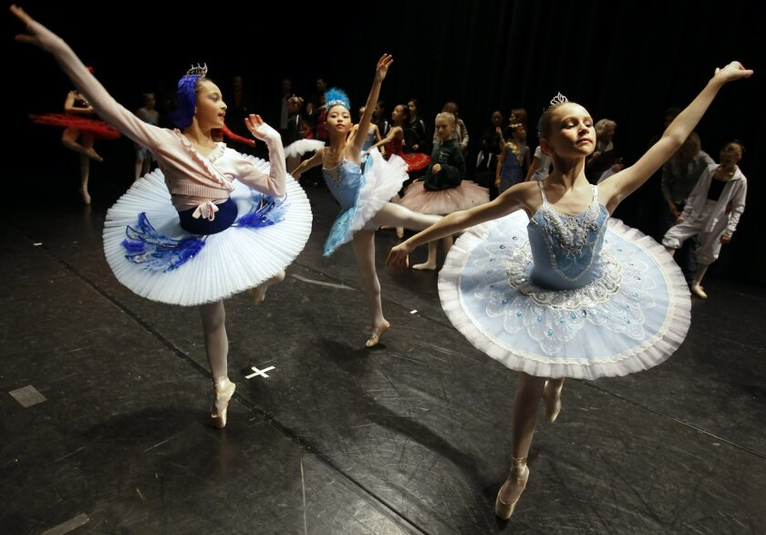 Ballet dancers, Malena Ani, Scarlet Wang, and Jordan Coutts warm up while waiting  for the Youth America Grand Prix 2013 semi-finals at Mater Dei Catholic High School in Chula Vista to begin.