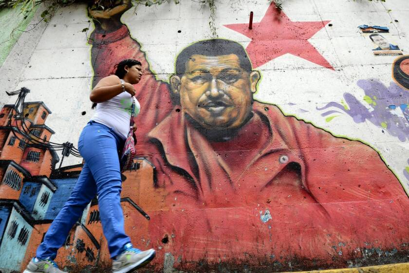A woman walks past a mural of Venezuelan President Hugo Chavez in Caracas, the capital, this week.