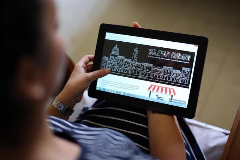 """Una joven cubana posa mostrando en una tableta la página de Bulevar Cubano, la primera tienda online """"Made in Cuba"""", el jueves, 15 de febrero de 2018, en La Habana (Cuba). EFE"""