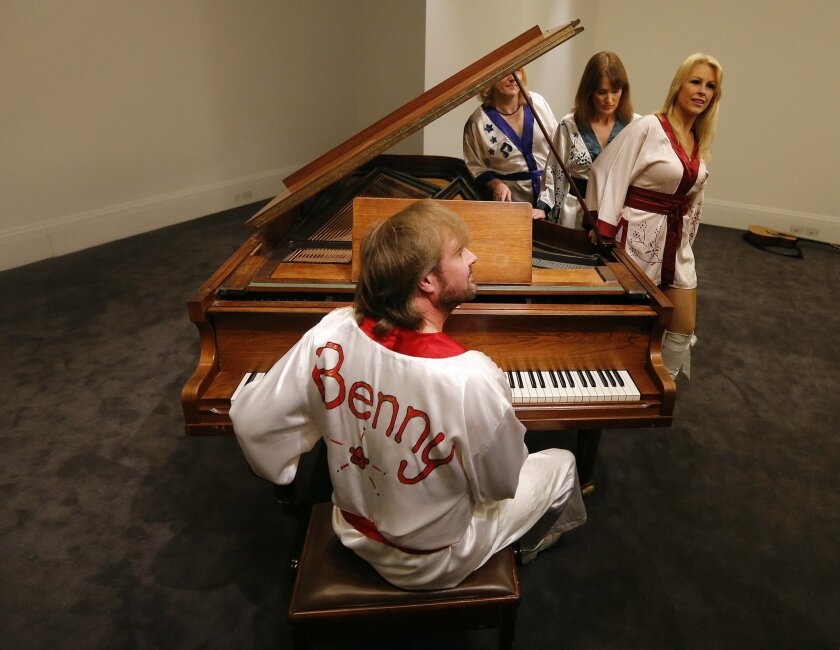 Actors of the ABBA show 'Bjoern Again' perform on a piano at Sotheby's auction house in London, Thursday, Aug. 27, 2015. A grand piano that featured on many of ABBA's biggest hits is going up for auction in London. Sotheby's is offering the instrument, owned by the Stockholm recording studio where the Swedish pop group often recorded. (AP Photo/Frank Augstein)